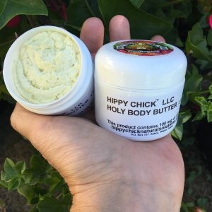 Hand holding 2 Holy Body Butter containers outside. One is open showing the product